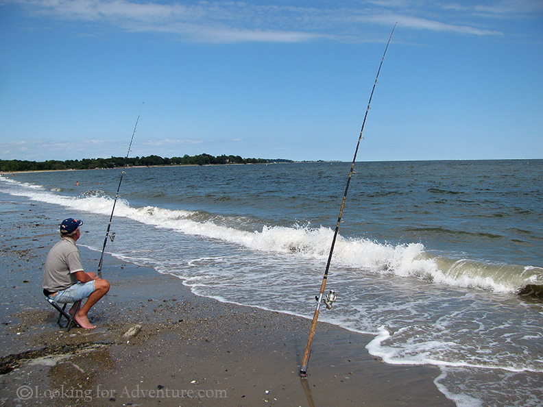 A man fishing on the beach with 2 fishing rods stuck in for Island beach state park fishing